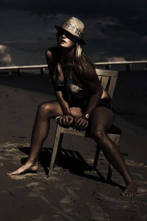 sombre: Creative Dark Fashion Portrait Of A Female Model Wearing Stylish Glamour Hat Modeling A Pose On A Wooden Chair During An Exotic And Moody Beach Photoshoot