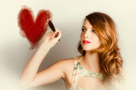 lovelorn: Young vintage woman painting a red heart with paint brush in a be my valentine concept Stock Photo