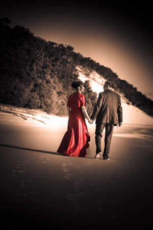 love life: Happy Wedding Couple Take A Casual Stroll Along The Beach Of Love In A Celebration Of A New Life Together In Marital Bliss