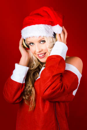 holiday music: Beautiful Young Woman Wearing Santa Claus Clothes Listening To Headphones On Red Christmas Background