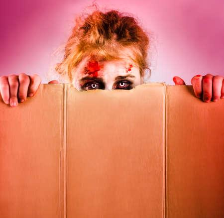 reanimated: Eerie monster peeking with evil eyes behind a blank board Halloween advertisement Stock Photo