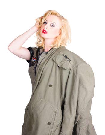militaire sexy: Belle jeune femme de l'arm�e avec des cheveux blonds sensuelle et classique permanent de maquillage en studio dans les v�tements militaires vieux de mode. 1940 d�crit la guerre de style pin-up r�tro Banque d'images
