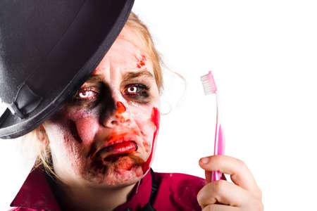 mujer golpeada: Aislado zombi femenina que sostiene un cepillo de dientes. Miedo al dentista