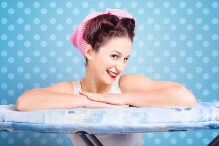 ama de casa: Retrato de ama de casa pinup alegre con glamorosos años 60 el peinado y maquillaje que descansa sobre la ropa tabla de planchar. Fondo azul de los lunares
