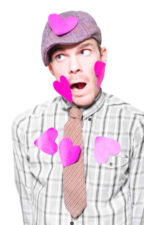 unattached: Surprised Young Man Covered With Love Heart Messages In A Depiction Of A Eligible Bachelor Or Heartthrob Isolated On White Background