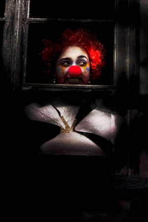 masquerader: Head Of A Clown Showing Through Dark Shadows Of An Old Window Stock Photo