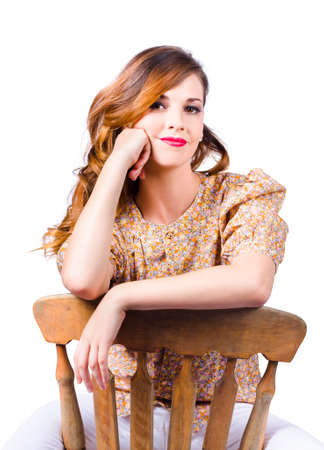 antique chair: Attractive smiling young woman at rest on antique wooden chair, white studio background.
