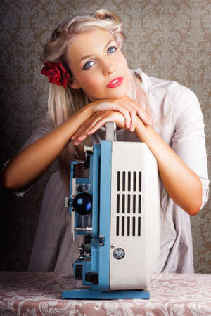 stardom: Beautiful Glamorous Young Blonde Starlet Leaning On Top Of An Old Reel To Reel Cine Projector Looking Up With A Dreamy Faraway Look Recalling Her Stardom