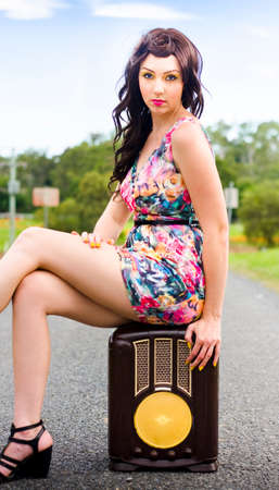 mini falda: Un hermoso y elegante morena mujer que llevaba un vestido floral de la vendimia con las cuñas que se sienta en un anticuado y Radio marrón antiguo Foto de archivo
