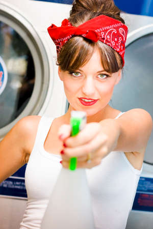 armed: Armed And Dangerous An Attractive Female Cleaning Lady Points A Bottle Of Disinfectant Cleaner While Smiling In A License To Clean Conceptual Stock Photo