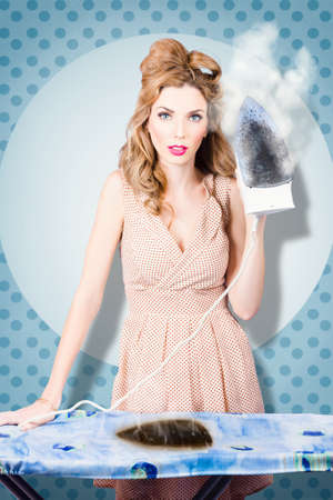 burnt out: Surprised housewife holding iron with cooked ironing board. Burnt out on house cleaning chores Stock Photo