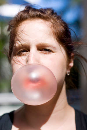 bubblegum: Lady Casually Blows Bubbles While Chewing Gum At A Outdoors Location Stock Photo