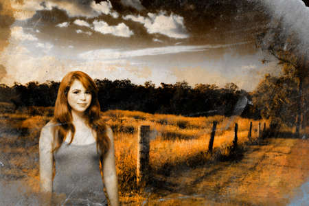 auburn hair: Cracked And Distressed Image Of A Happy Young Country Girl With Auburn Hair Standing At A Rural Farm Location During Sunset Stock Photo