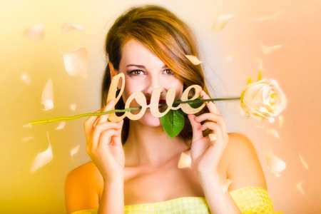 tryst: Young woman standing under a fall of flower petals holding white rose entwined with love text on yellow background Stock Photo