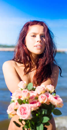 woebegone: Attractive Young Girl Standing By The Sea Holds Out A Bunch Of Flowers When Giving The Gift Of Love In The Tender Rose Bouquet Offering Stock Photo