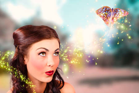 nature woman: Fine art beauty and fashion portrait of a fairy tale girl with amazing makeup watching magic butterflies spiral light in a colorful spring garden. Fantasy design
