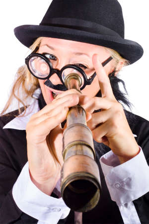disguised: Businesswoman in bowler hat and dark suit with thick rimmed glasses, fake mustache looking through antique telescope
