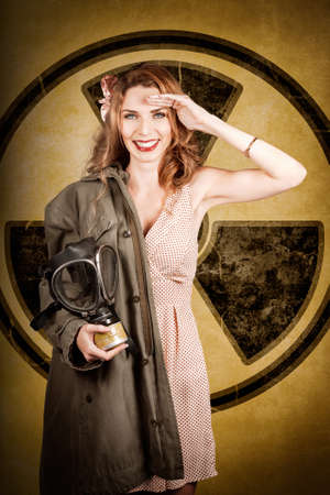 bombshell: Old-fashion photograph of a military pin-up woman saluting with allied gas mask in front of a nuclear radiation symbol. Atomic female bombshell