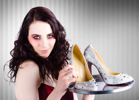 saleslady: Beautiful fashion sales woman wearing bright make-up holding a silver platter of shoes when selling luxurious evening attire Stock Photo