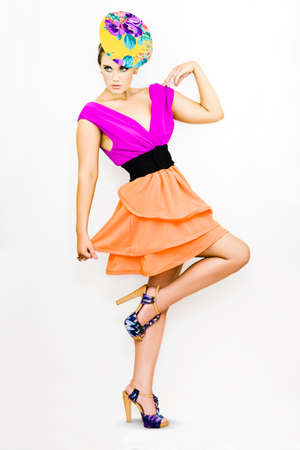 voguish: Studio Picture Of A Pretty Model Wearing Bright Fashion With Colourful Hat Balancing On One Foot With Poise In A Retro Fashion Dance Conceptual White Background