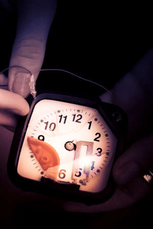 shadowy: Closeup Of Hands Holding A Broken Analog Clock  Dark Background