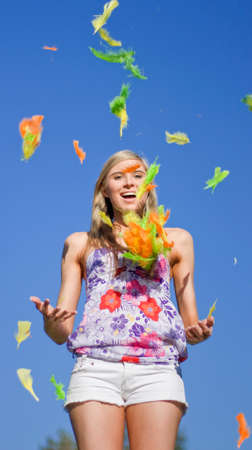 hurl: As Light As A Feather A Woman Playfully Throws Feathers Into The Sky And Joyfully Watches Them Gracefully Glide Down To The Ground Stock Photo