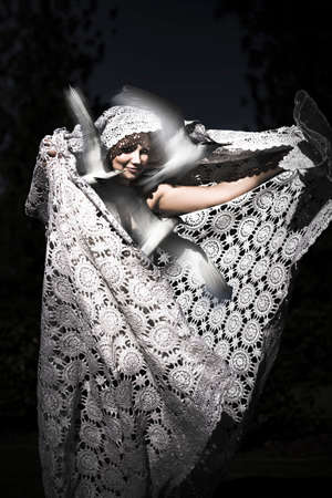 seductress: Silver Seductress On Black, dramatic portrait of a beautiful woman draped in flowing patterned shawl releasing birds in a freedom concept