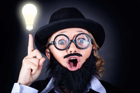 got: Crazy male scientist wearing nerd glasses, fake moe and plastic beard pointing up to bright lightbulb with expression of genius. Science Innovation concept