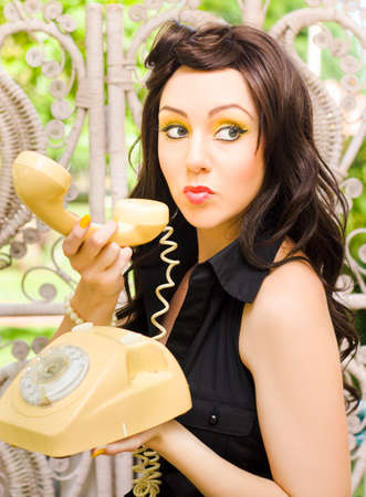 waiting glance: Anxious And Nervous Pretty Brunette Woman Glances Over Her Should With A Sneaky And Mischievous Expression While Making A Phone Call On A Retro Telephone Stock Photo