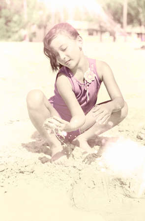 yellowed: Faded Artistically Aged And Yellowed Image Of A Young Retro Girl Sitting Playing In Beach Sand In A Nostalgia And Memorabilia Concept Stock Photo