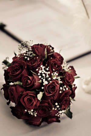 olden day: Vintage Red Rose Flower Bouquet Laying On A Table Next To The Wedding Register Booklet In A Wedding Moment Image