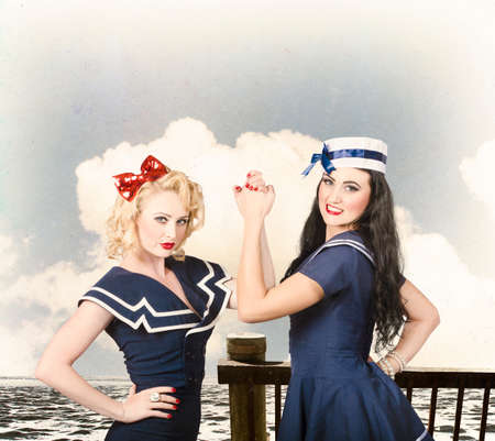 wrestle: Vintage fashion fight. Beautiful young women with pinup hairstyle and makeup in an arm wrestle competition outdoors at a retro sea dock