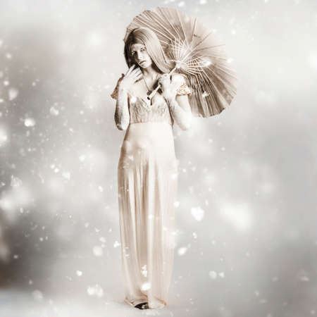 dramatic characters: Fine art horror portrait of a scary ghost woman holding oriental parasol on a cold snowing winter landscape. The white vampire