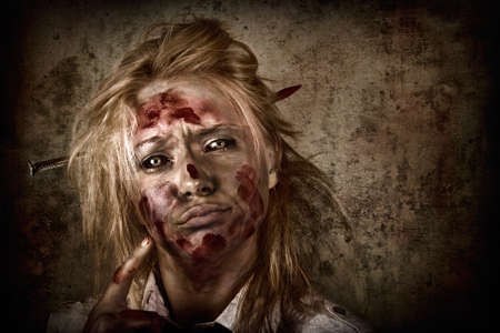 grisly: Dark horror portrait of a sinister female zombie businesswoman thinking up a sharp idea with nail through head on grunge background