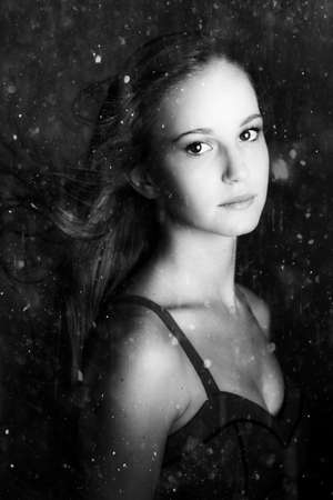 quietude: Monochrome portrait of a beautiful young woman displaying sorrow sadness and desolation while motioning from an oncoming storm when running from the rain