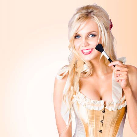 performing arts: Young blonde beauty applying make up with cosmetics brush. Performing arts stage makeup concept