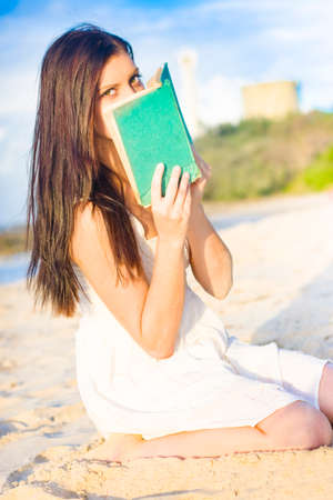 scared girl: Frightened And Scared Girl Hiding Behind A Green Book Or Novel While Kneeling In The Sand At A Beach Seashore Location Stock Photo