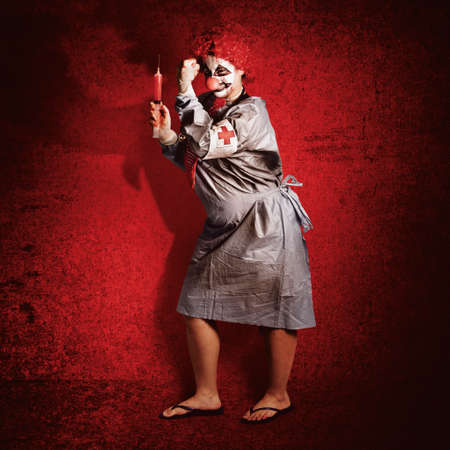 clowning: Scary clown doctor holding large medical syringe about to give a jab on red cement wall. Evil medicine Stock Photo