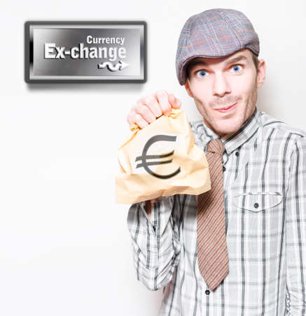 laidoff: Man In Recession Clothing Holding Bag Of Euro Currency At Money Exchange In A Depiction Of The European Sovereign Debt Crisis Or Eurozone Crisis Stock Photo