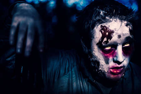 infectious: Creepy night photo of a scary zombie looking gravely ill with infectious facial wounds walking through moonlit forest. Attack of the killer monsters Stock Photo