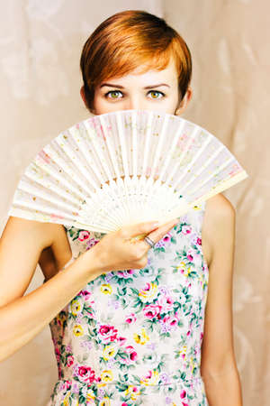 splayed: short-haired girl wearing a floral dress covering her mouth with a oriental fan in a beautiful secret conceptual