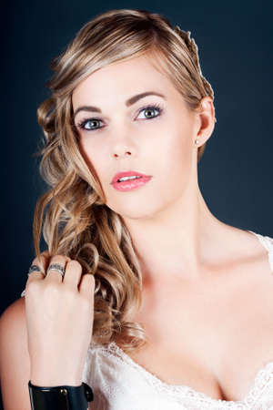 beautify: Beautiful Glamorous Radiant Bride With Lovely Smooth Complexion And Natural Makeup Wearing A Stylish Off The Shoulder Dress Twirling Her Curly Long Blonde Hair On Dark Background Stock Photo