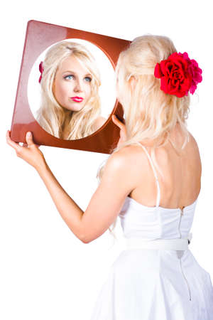 admires: Beautiful young blond woman looking at reflection in mirror, white background