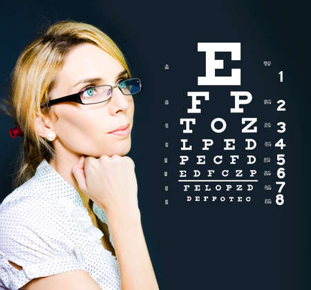 eye chart: Photo Of A Beautiful Blonde Business Optician Or Optometrist Wearing Eye Wear Glasses Looking At Number And Letters On A Ophthalmology Chart To Check Eyesight Stock Photo