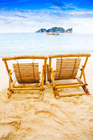 recliner: Two Wooden Recliner Chairs Sit On A Thailand Tropical Island Beach Location With Longboat On The Distant Waters, Photograph Taken Phi Phi Island Thailand Stock Photo