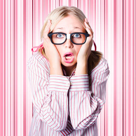 consternation: Dorky woman wearing spectacles clutching head with look of panic when making a difficult business decision