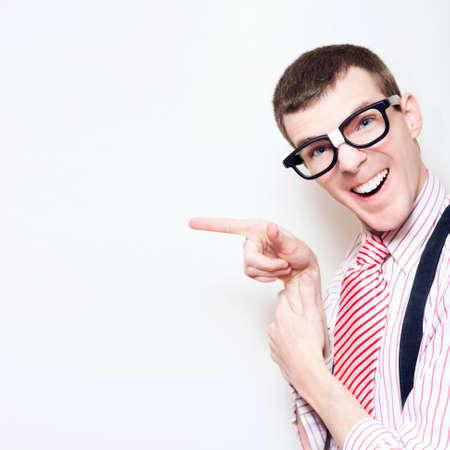 estereotipo: Feliz Riendo friki del ordenador El uso Estereotipo gafas, corbata a rayas y señalando en blanco pared Publicidad Copyspace