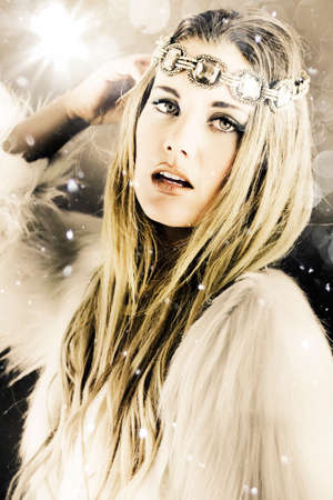 enchanting: Artistically toned image in cool tones of a beautiful blonde woman in white with a jewelled headband standing under falling snowflakes during winter in a enchanting snow princess concept