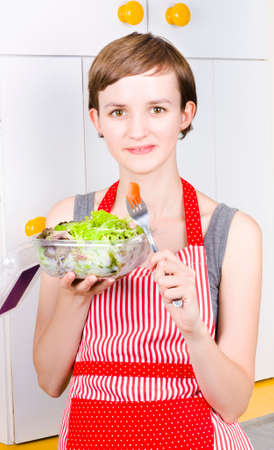 health conscious: Health conscious woman eating green leaves salad with chunks of fresh tomato in a dieting and nutrition concept
