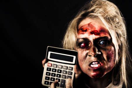 debt: Mad undead business woman having financial difficulty pressing button on a recession calculator. Halloween sale